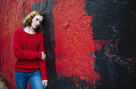 Woman leans against red painted mural in alley uptown Minneapolis, Minnesota portrait headshots