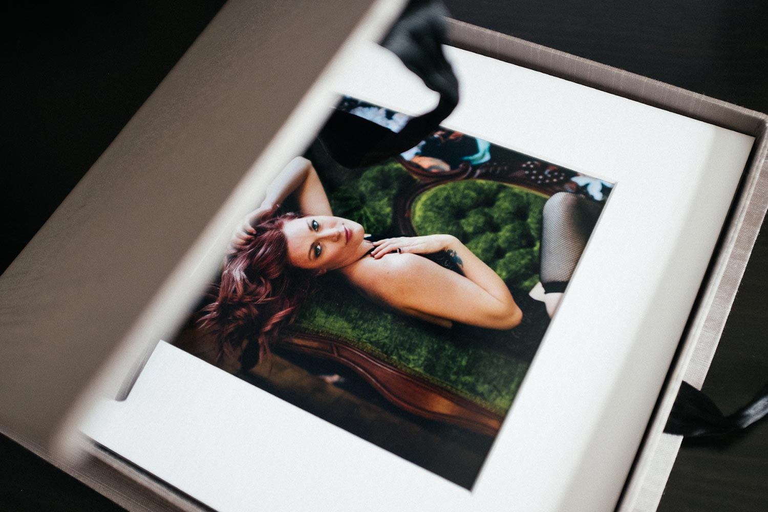 Opened view of 10x10 fine art print box, with 6x6 prints matted in a white frame. Twin Cities Boudoir Photographer