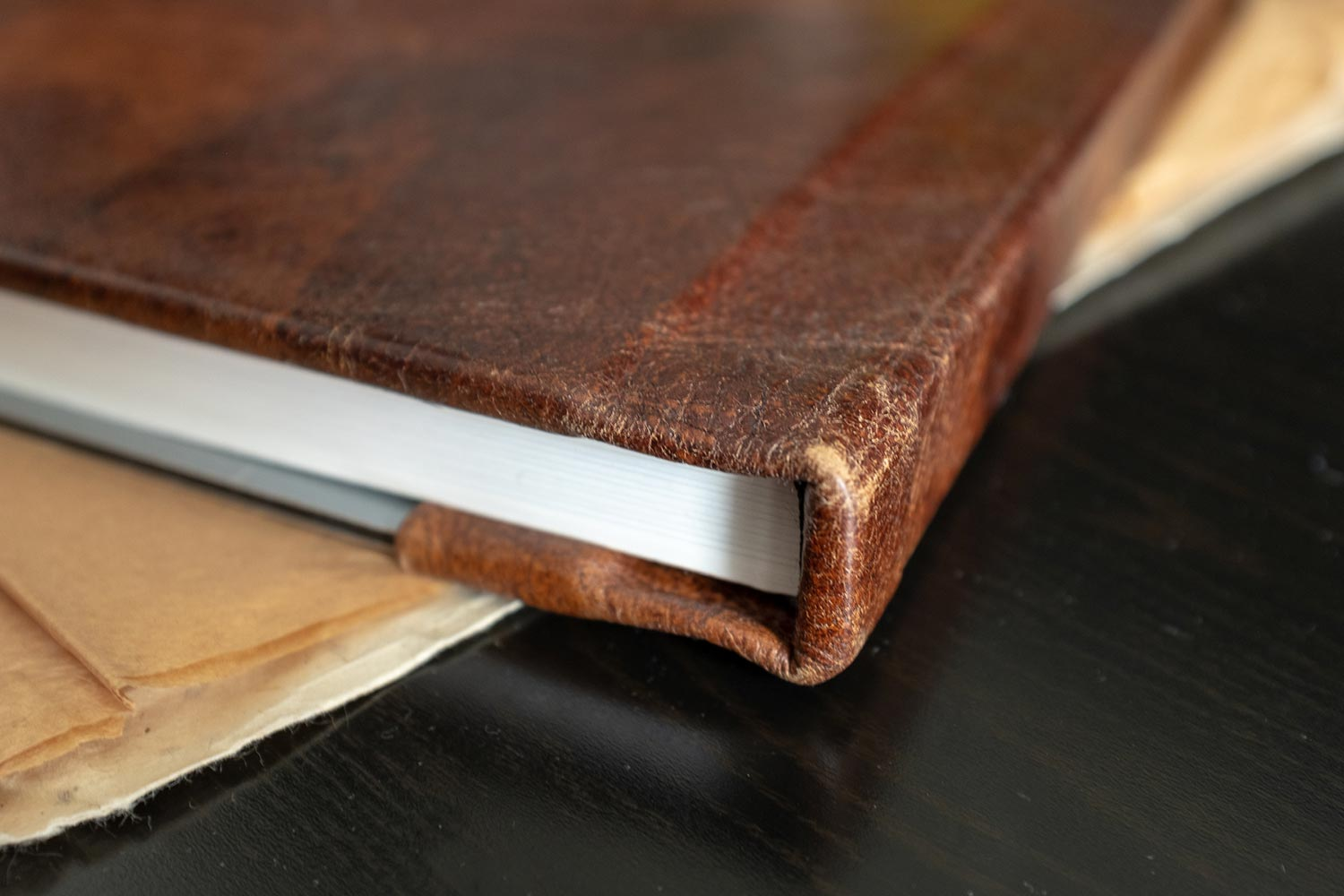 Fancy wedding album with a metal cover and vintage brown leather binding. Midwest Wedding Photographer
