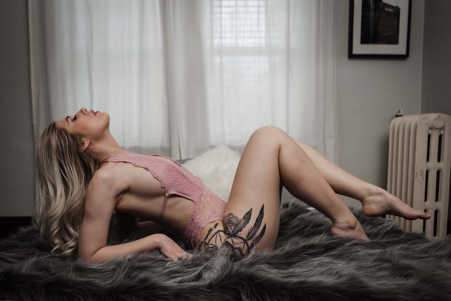Woman with hip tattoo lays on bed with faux fur throw. Intimate portrait boudoir photography photographers. Twin Cities Boudoir Photographer