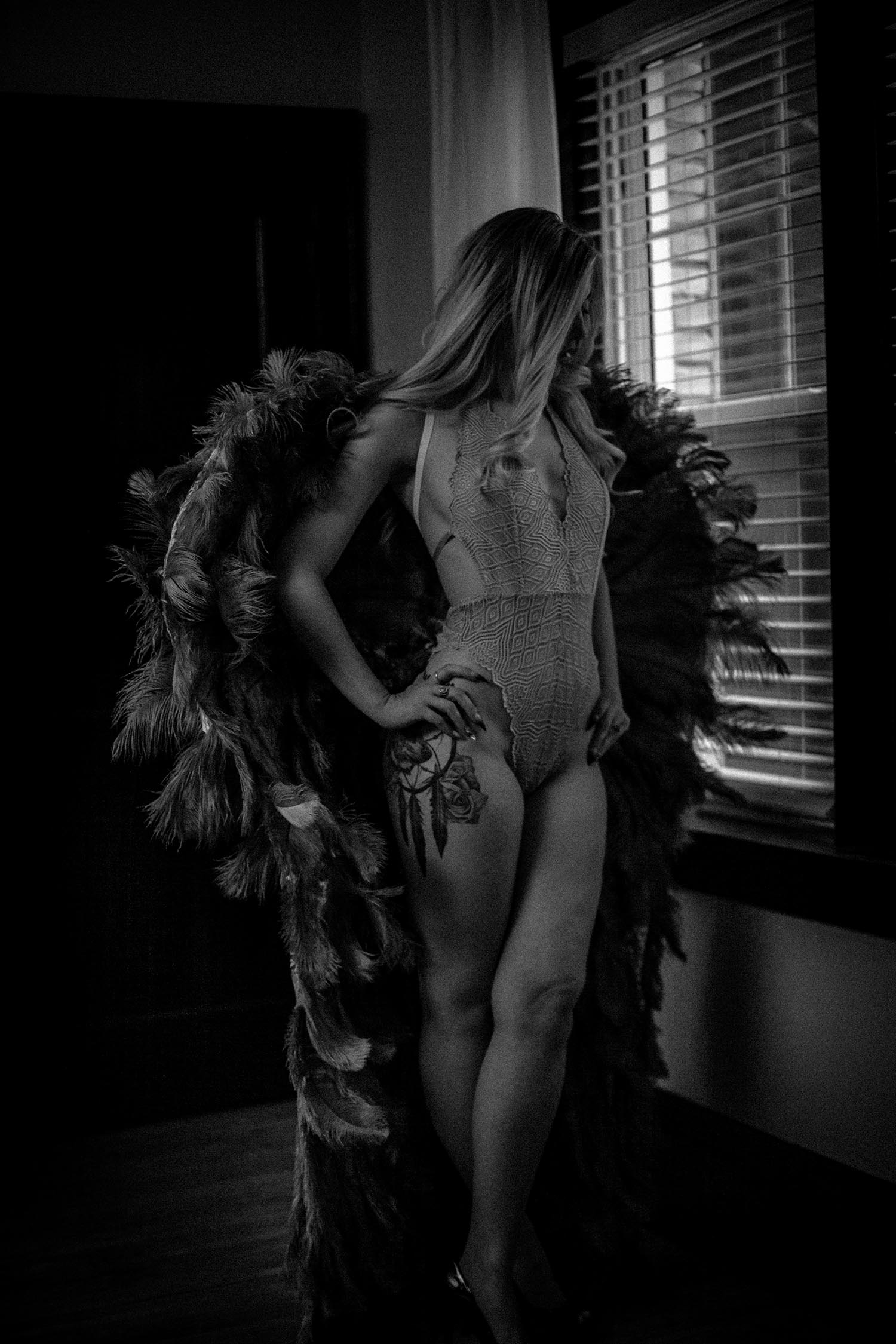 Dark moody black and white intimate portrait  with angel wings, using window light. Twin Cities Boudoir Photographer