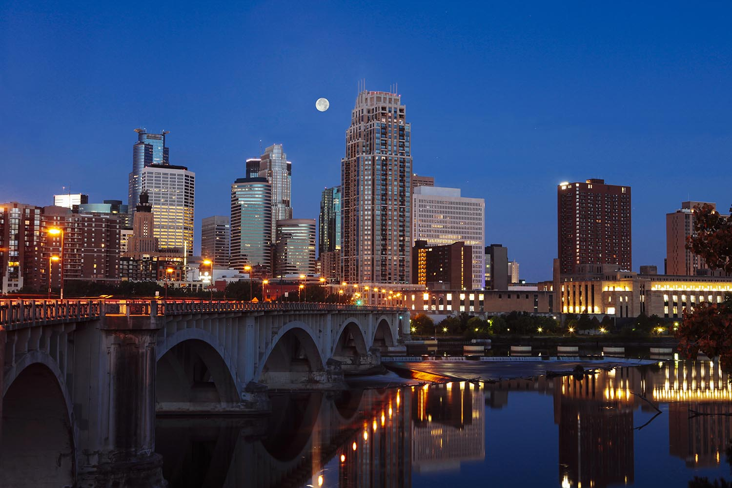 Minneapolis, Minnesota skyline with the Central SE bridge and Mississippi river in the early morning with the full moon. Grand Opening