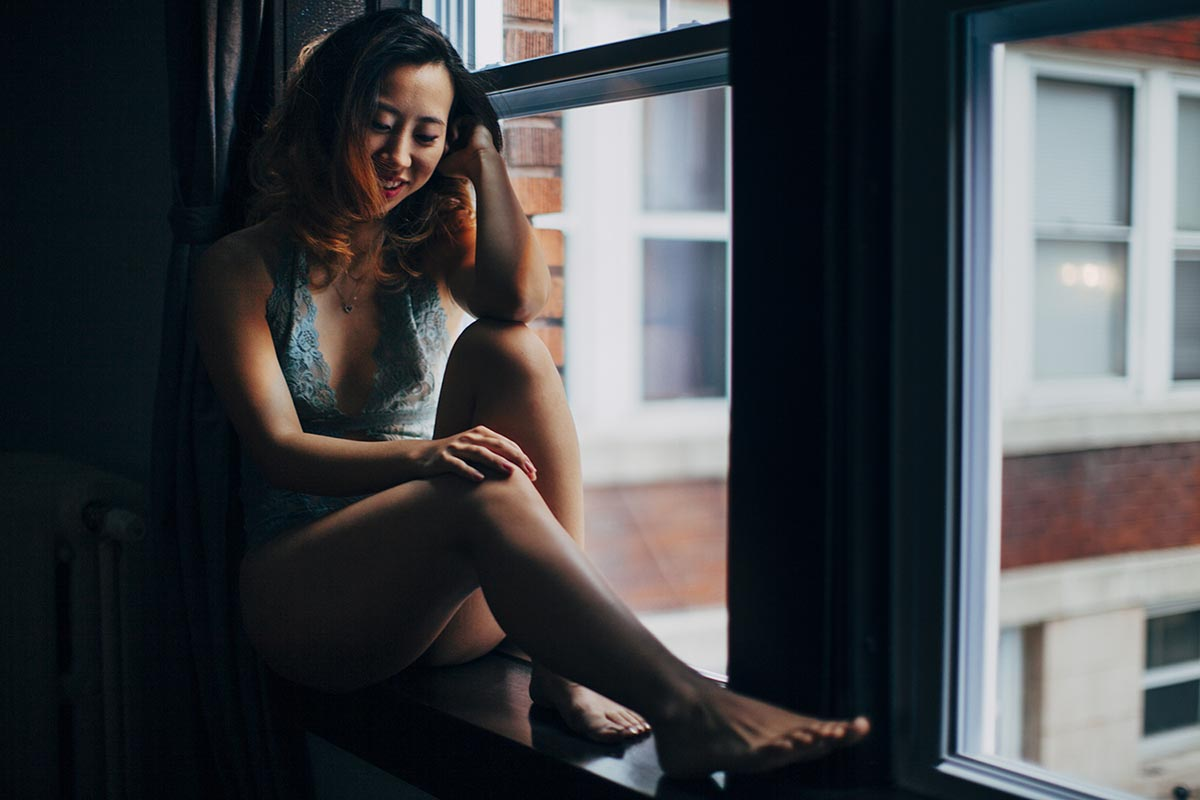 Woman sitting in window Minnesota Boudoir Photographer Fun Candid
