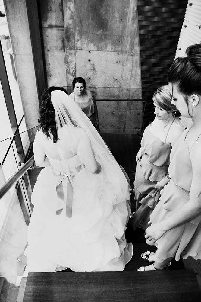 Black and white portrait of bridal party as bride walks down stairs, documentary wedding photography. Saint Paul Photographers