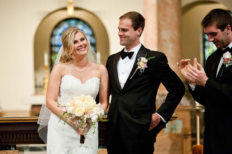 Newly weds end of Catholic wedding ceremony. Candid documentary photo, best man clapping