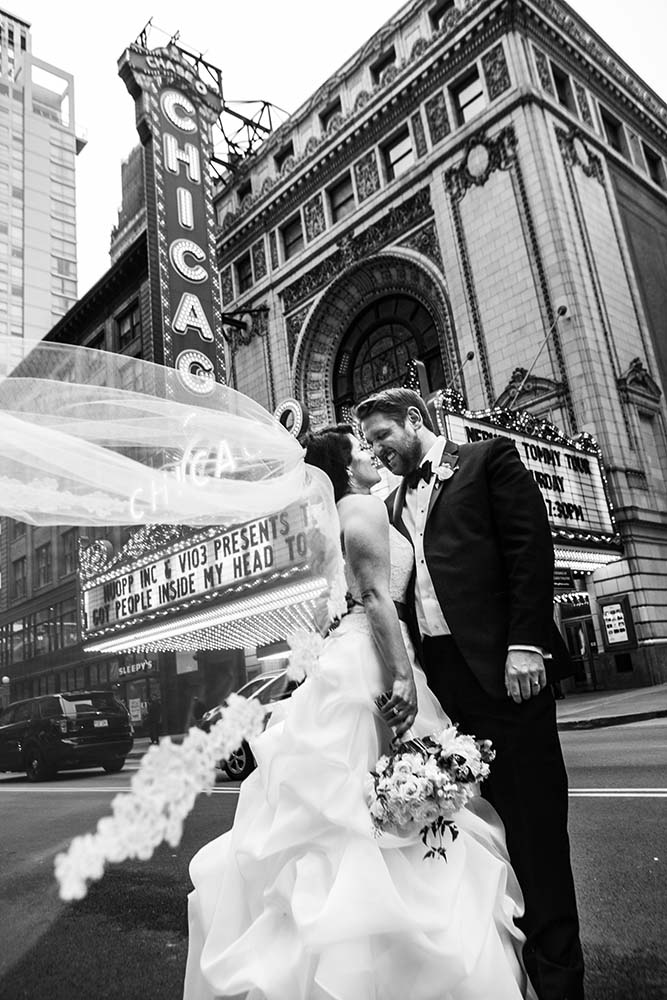 Black and white portrait of Bride and Groom  in front of Chicago Theater . Chicago Wedding Photographer