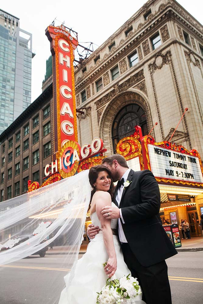 portrait of Bride and Groom  in front of Chicago Theater  Marquee. Chicago Wedding Photographer