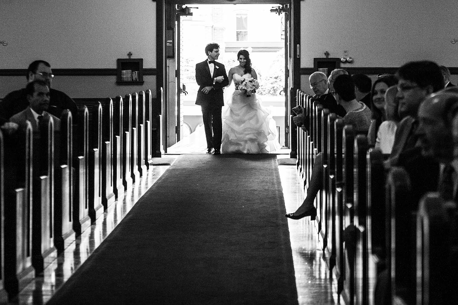 Black and white portrait of bride and father of the bride walk down the aisle. Minneapolis Wedding photography