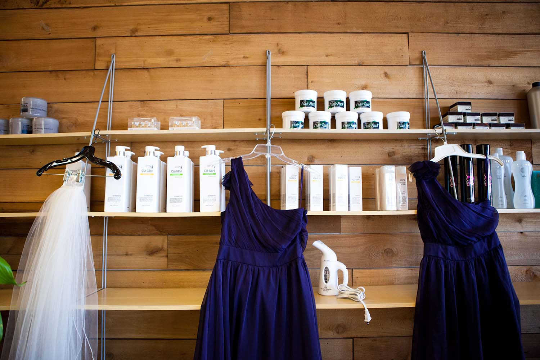Bridal veil and blue bridesmaid dresses hang at salon. Wedding day photojournalism. Twin Cities Wedding Photography
