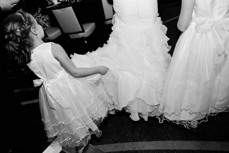 flower girls holds bridal gown. Wedding photo documentary. Twin Cities Wedding Photographers