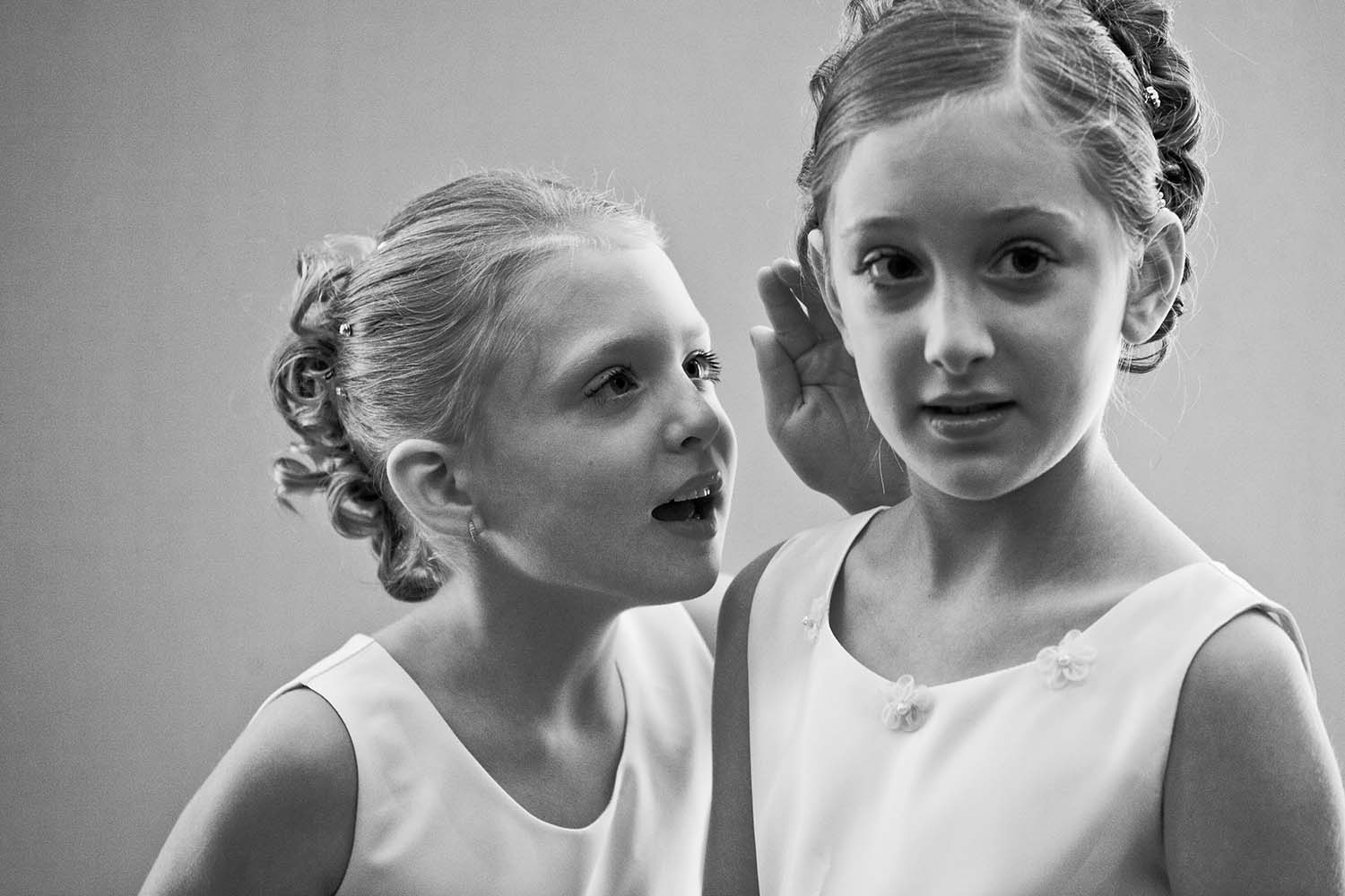 Flower girl whispering to each other, documentary wedding photography, candid wedding photograph