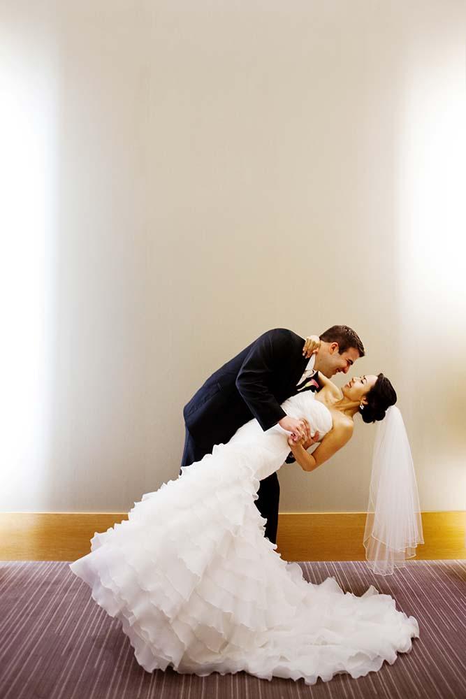 Groom dipping bride, wedding day photography, hotel lobby, Minnesota Wedding Photographer