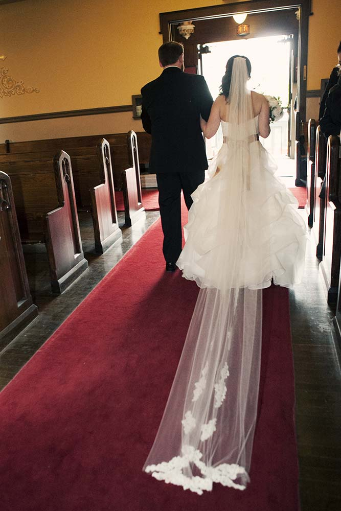 Newlyweds walk out of church after wedding ceremony. Twin Cities Wedding Photographer