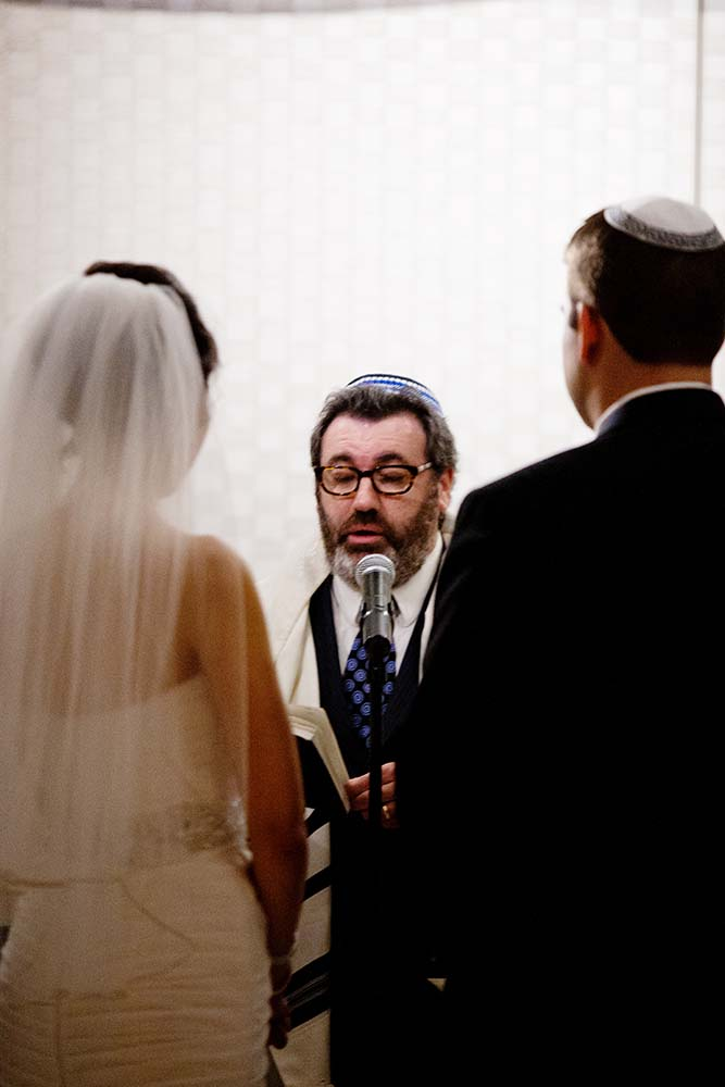 Rabi conducting Jewish wedding ceremony with bride and groom