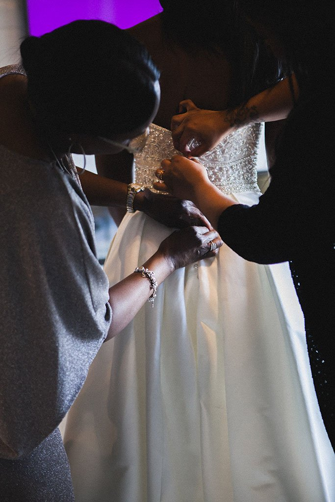 Bride wedding dress documentary photo hands buttoning