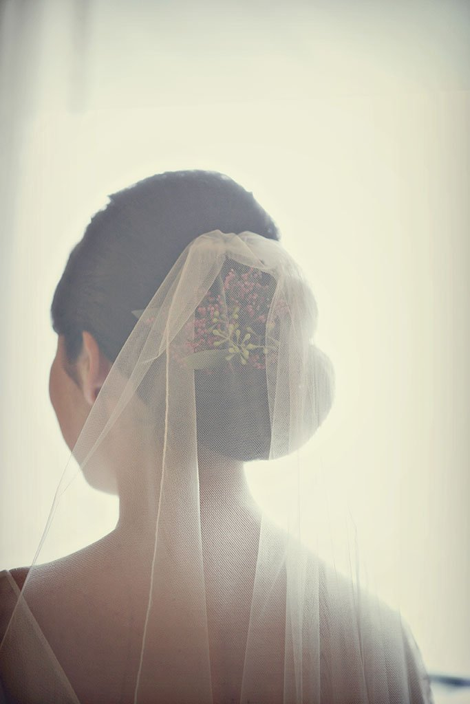 Detail of brides wedding veil and purple flowers in her hair, vintage toned