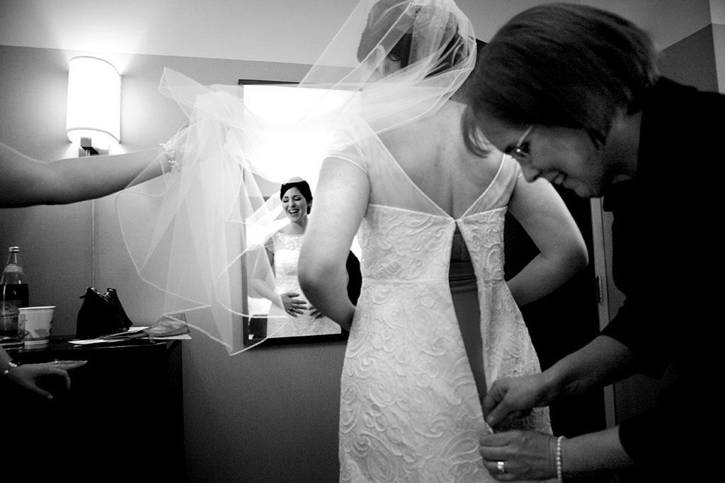 Mother of the bride zipping up the wedding dress, getting ready candid wedding photography